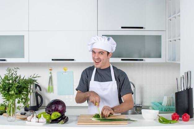 Vue de face heureux chef masculin en uniforme coupant les verts sur une planche de bois derrière la table de la cuisine