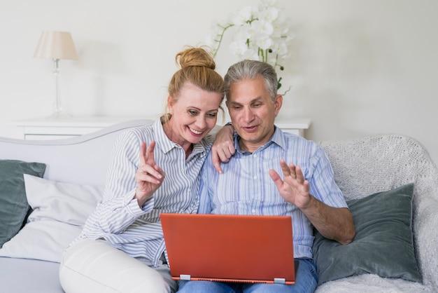 Vue de face heureux couple de personnes âgées avec un ordinateur portable