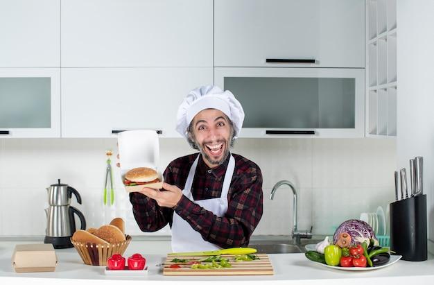 Vue de face heureux cuisinier mâle brandissant un hamburger dans la cuisine