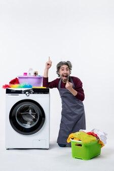 Vue de face heureux homme de ménage debout sur le genou pointant avec le doigt vers le haut sur fond blanc