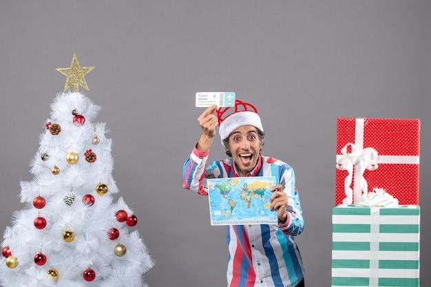 Vue de face heureux jeune homme avec bonnet de noel printemps spirale tenant carte du monde et billet de voyage