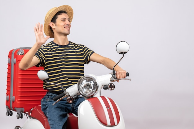 Vue de face de l'heureux jeune homme avec chapeau de paille sur un cyclomoteur en agitant la main