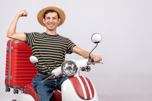 Vue de face de l'heureux jeune homme avec chapeau de paille sur cyclomoteur montrant le muscle du bras