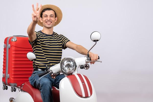 Vue de face de l'heureux jeune homme avec un chapeau de paille sur un cyclomoteur vous montrant les doigts