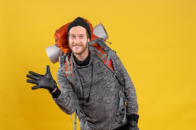 Vue de face de l'heureux jeune homme avec des gants en cuir et un sac à dos en agitant la main