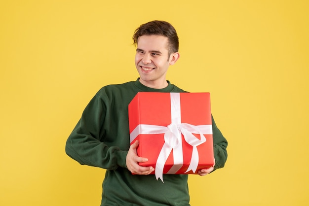 Vue de face heureux jeune homme avec pull vert tenant un cadeau de noël sur jaune
