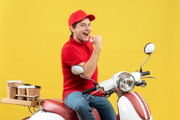 Vue de face de l'heureux jeune homme souriant portant un chemisier rouge et un chapeau livrant des commandes sur fond jaune