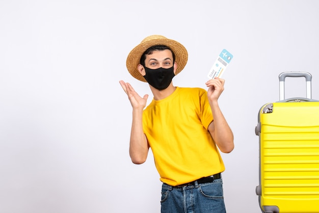 Vue de face heureux jeune homme en t-shirt jaune debout près de valise jaune tenant un billet de voyage