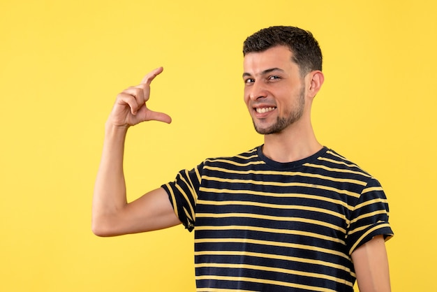 Vue de face heureux jeune homme en t-shirt rayé noir et blanc fond isolé jaune