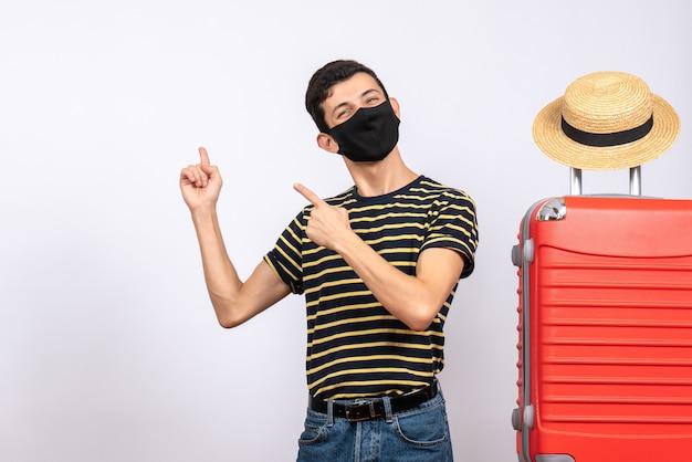 Vue de face heureux jeune touriste avec masque noir debout près de valise rouge pointant derrière