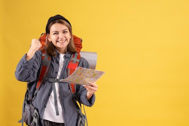 Vue de face de l'heureux jeune voyageur avec sac à dos tenant la carte