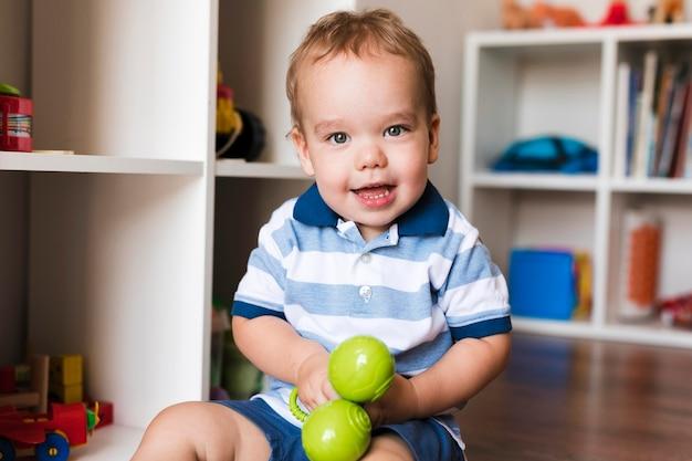 Vue de face de l'heureux petit garçon mignon jouant avec des jouets