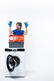 Vue de face heureux réparateur levant la machine à laver les mains sur un espace blanc