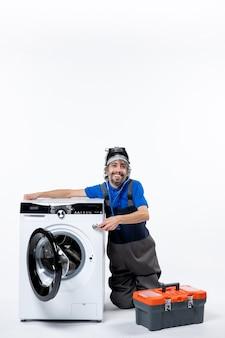 Vue de face heureux réparateur tenant une rondelle sur un espace blanc
