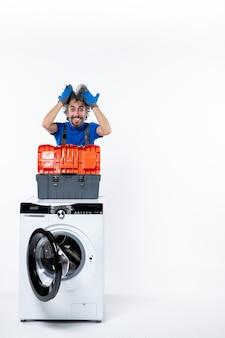 Vue de face heureux réparateur tenant un sac à outils pour cheveux sur une machine à laver sur un espace blanc