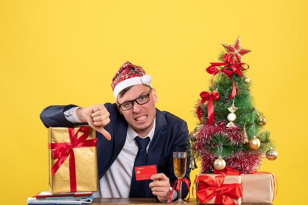 Vue de face de l'homme d'affaires avec bonnet de noel faisant le pouce vers le bas signe assis à la table près de l'arbre de noël et présente sur jaune