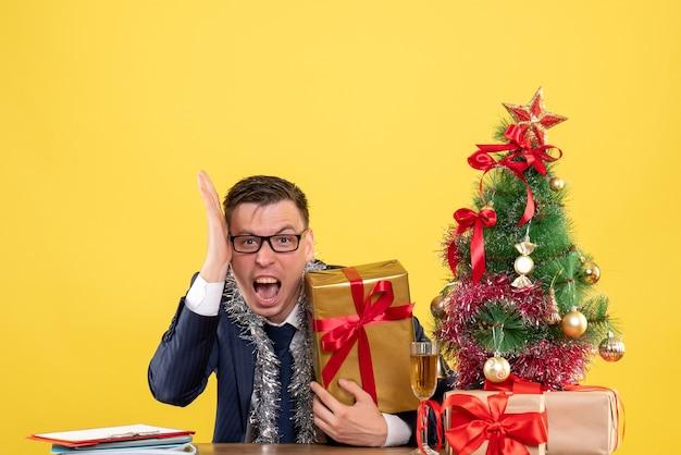 Vue de face de l'homme d'affaires en colère assis à la table près de l'arbre de noël et présente sur le mur jaune