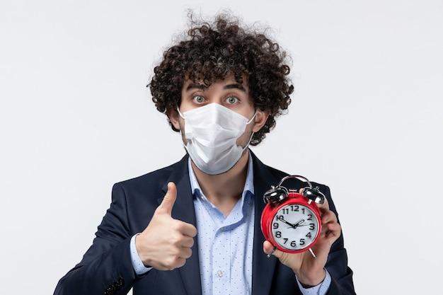 Vue de face d'un homme d'affaires confiant en costume et portant son masque tenant une horloge faisant un geste correct