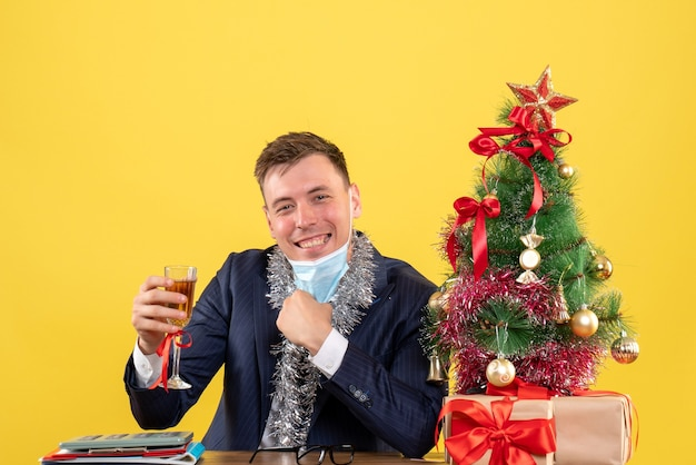 Vue de face de l'homme d'affaires décollant son masque assis à la table près de l'arbre de noël et présente sur jaune.