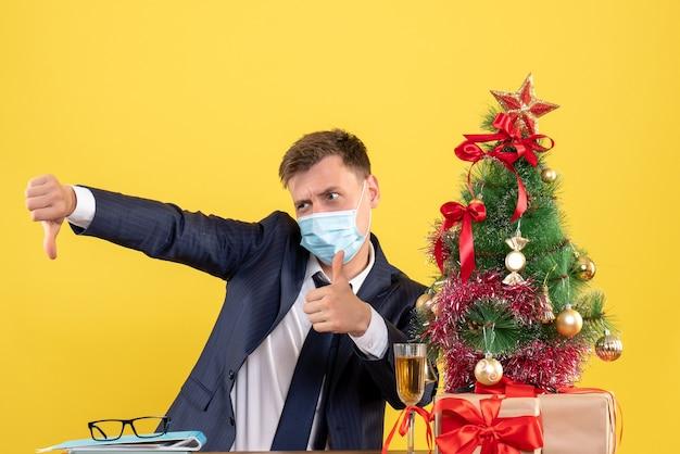 Vue de face de l'homme d'affaires faisant le pouce de haut en bas signe assis à la table près de l'arbre de noël et présente sur jaune