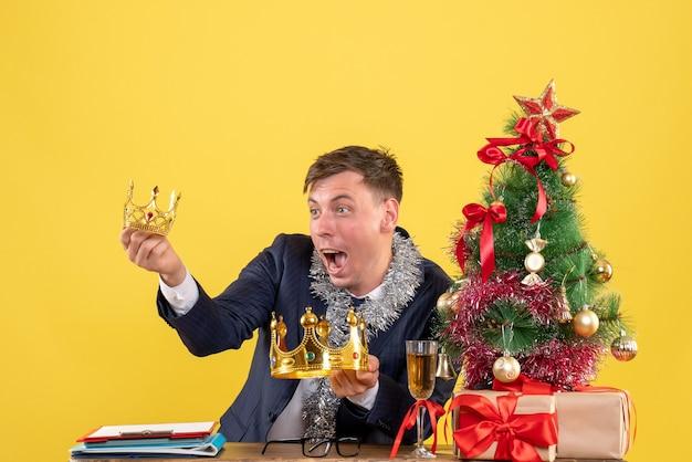 Vue de face de l'homme d'affaires à la recherche de couronnes assis à la table près de l'arbre de noël et présente sur jaune