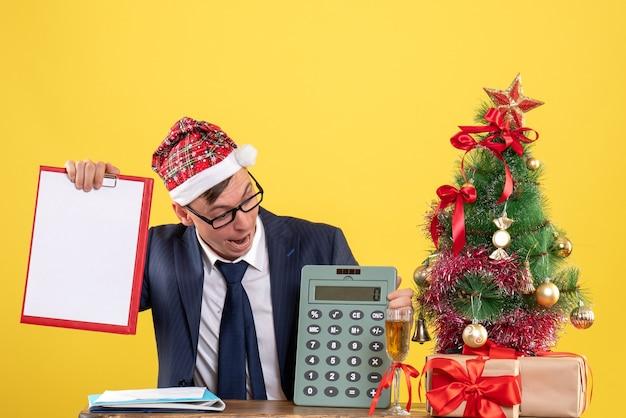 Vue de face de l'homme d'affaires regardant la calculatrice assis à la table près de l'arbre de noël et présente sur jaune