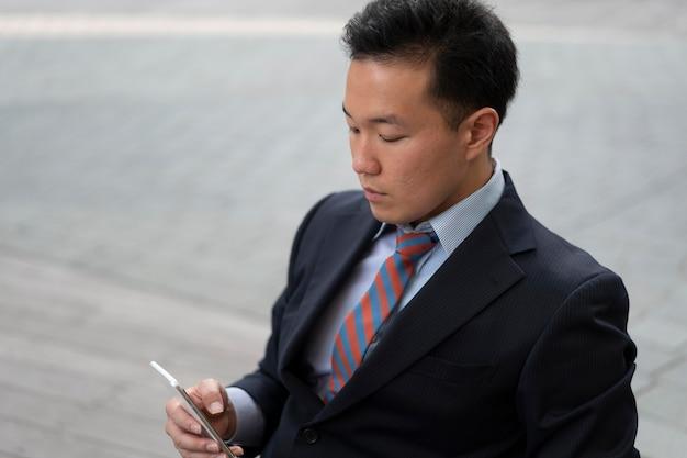 Vue de face de l'homme d'affaires avec smartphone