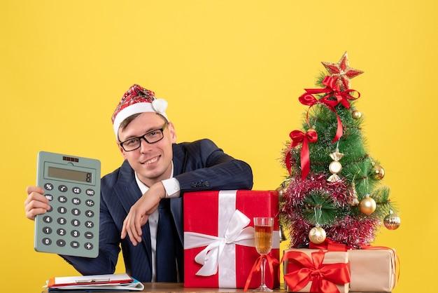 Vue de face de l'homme d'affaires tenant la calculatrice assis à la table près de l'arbre de noël et présente sur jaune.