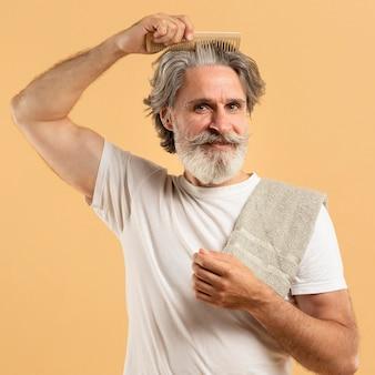 Vue de face d'un homme âgé avec barbe se peignant les cheveux
