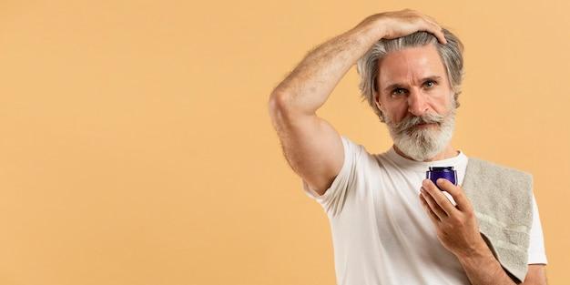 Vue de face d'un homme âgé avec barbe tenant une crème hydratante
