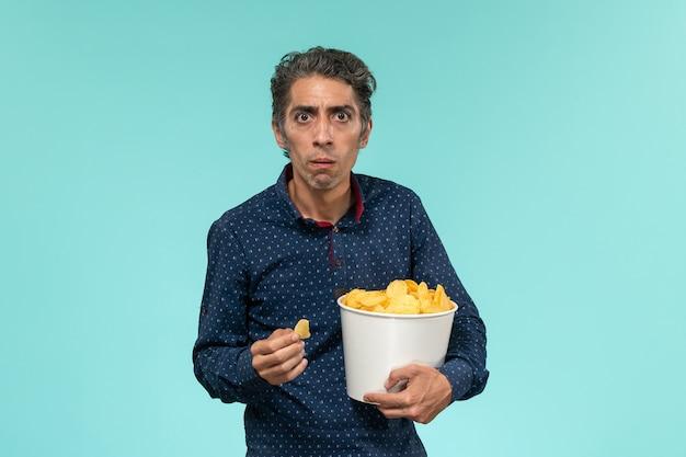 Vue de face homme d'âge moyen avec panier plein de cips sur bureau bleu