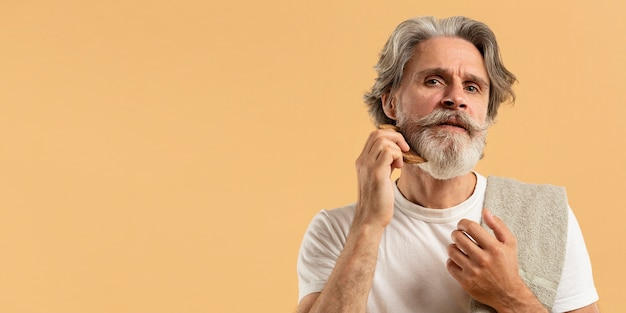 Vue de face d'un homme âgé peignant la barbe avec copie espace