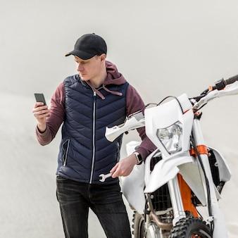 Vue de face homme appelant à l'aide pour réparer une moto