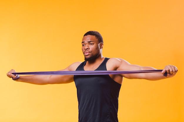 Vue de face de l'homme athlétique en tenue de sport avec bande de résistance