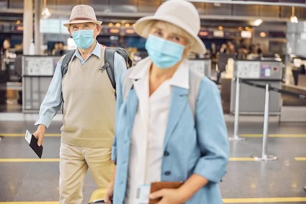 Vue de face d'un homme aux cheveux gris et d'une dame âgée avec leurs cartes d'embarquement et leurs bagages