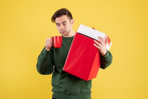Vue de face homme aux yeux écarquillés avec pull vert tenant un gros cadeau et une tasse rouge debout sur jaune