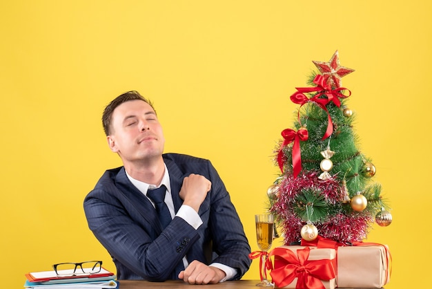 Vue de face de l'homme aux yeux fermés mettant la main sur sa poitrine assis à la table près de l'arbre de noël et des cadeaux sur jaune