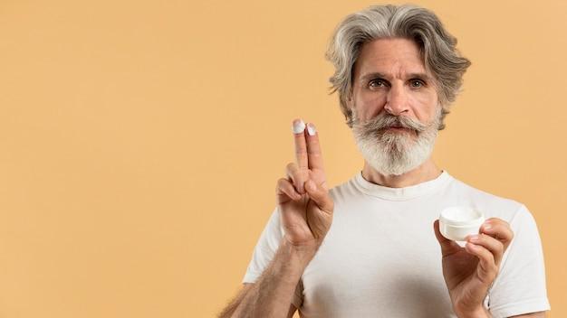 Vue de face de l'homme barbu aîné avec crème hydratante et copiez l'espace