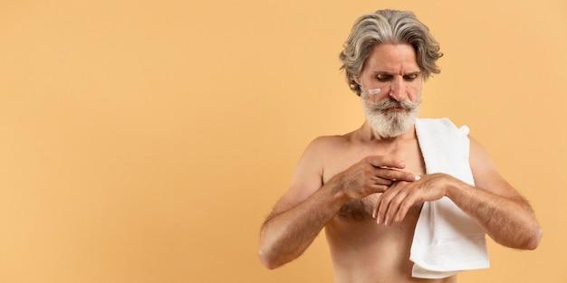 Vue de face de l'homme barbu aîné avec une serviette appliquant la crème avec copie espace