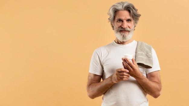 Vue de face de l'homme barbu aîné tenant une crème hydratante avec copie spadce