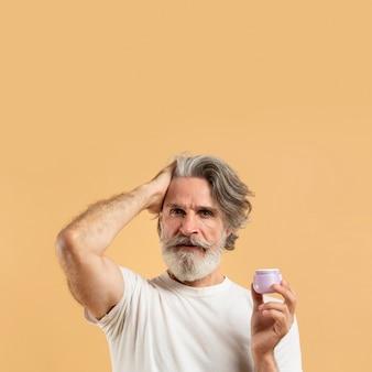 Vue de face de l'homme barbu aîné tenant le gel capillaire