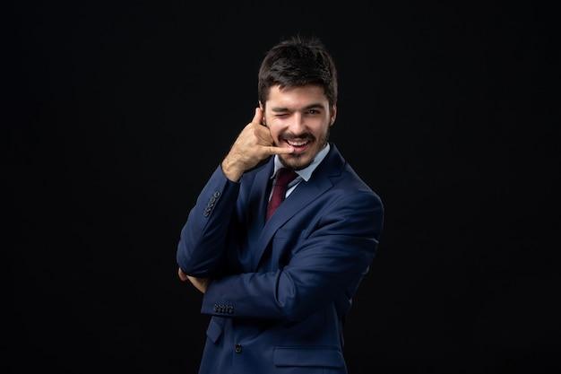 Vue de face d'un homme barbu émotionnel faisant un geste de lunettes sur un mur sombre isolé