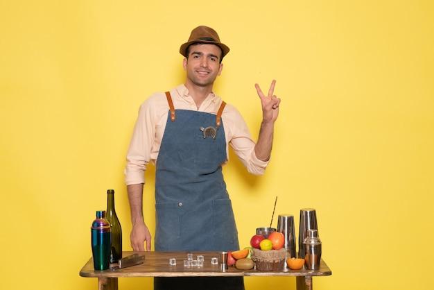 Vue de face homme barman debout devant le bureau avec des boissons et des fruits souriant sur un mur jaune boisson night club bar à jus homme