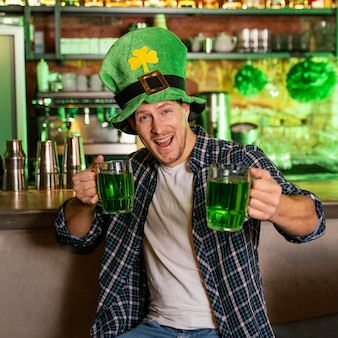 Vue de face de l'homme célébrant st. patrick's day au bar avec boissons