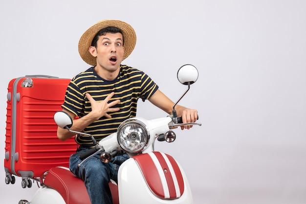 Vue de face de l'homme choqué avec chapeau de paille sur cyclomoteur