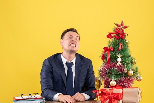 Vue de face de l'homme en colère assis à la table près de l'arbre de noël et présente sur le mur jaune copie place