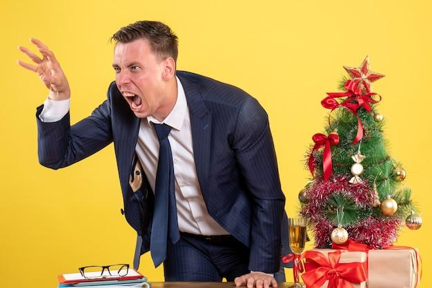 Vue de face de l'homme en colère debout derrière la table près de l'arbre de noël et présente sur mur jaune