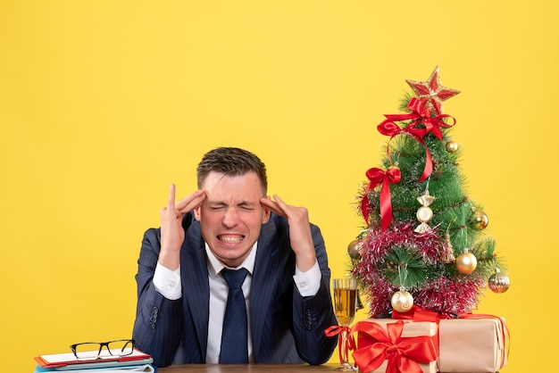 Vue de face de l'homme en colère mettant les doigts à son temple assis à la table près de l'arbre de noël et des cadeaux sur le mur jaune