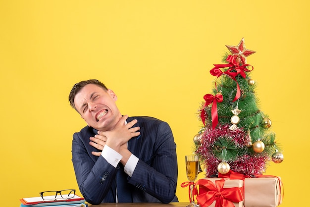 Vue de face homme en colère s'étranglant avec les deux mains assis à la table près de l'arbre de noël et des cadeaux sur fond jaune