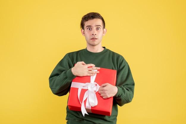 Vue de face homme confus avec pull vert tenant cadeau sur jaune